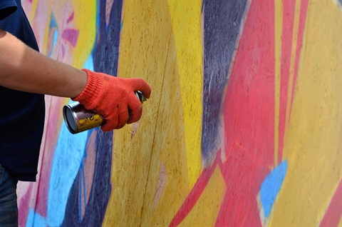 An artist holds a spray paint can to a colourful mural.