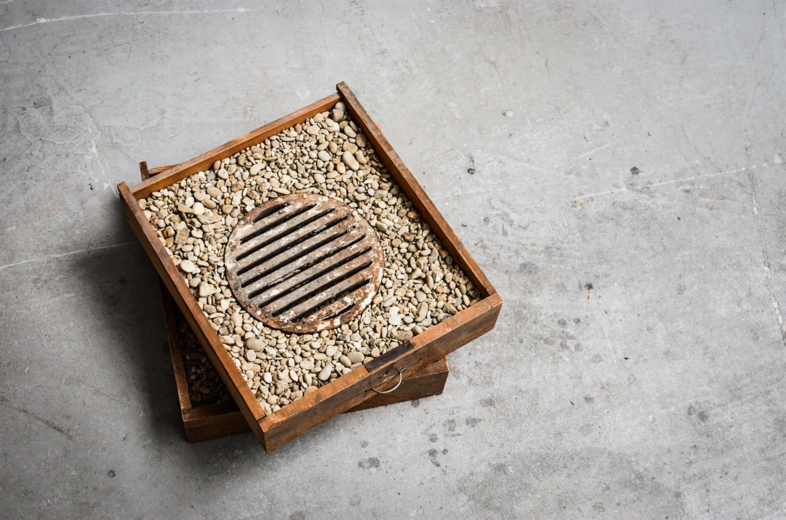 Johnathan Kim .Wood, Stone & Steel I, 2019, found drawer, pebble and grate, 56x56x22cm. Image courtesy of artist